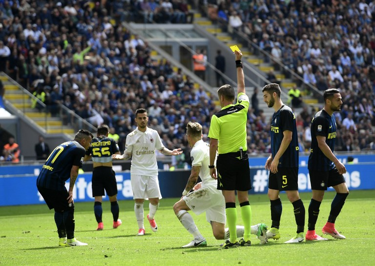 AC Milan's Slovenian midfielder Juraj Kucka receives a yellow card during the Italian Serie A football match Inter Milan vs AC Milan at the San Siro stadium in Milan on April 15, 2017. / AFP PHOTO / MIGUEL MEDINA