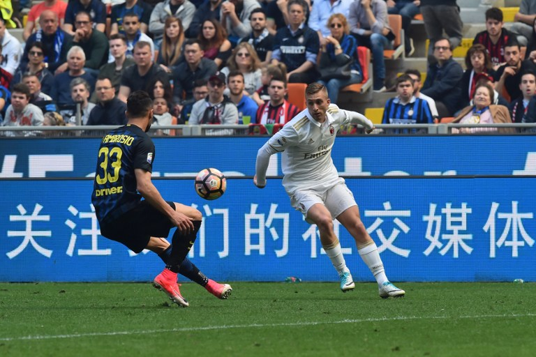 """AC Milan's midfielder from Spain Gerard Deulofeu (R) fights for the ball with Inter Milan's defender from Italy Danilo D'Ambrosio during the Italian Serie A football match Inter Milan vs AC Milan at """"San Siro"""" Stadium in Milan on April 15, 2017. / AFP PHOTO / GIUSEPPE CACACE"""