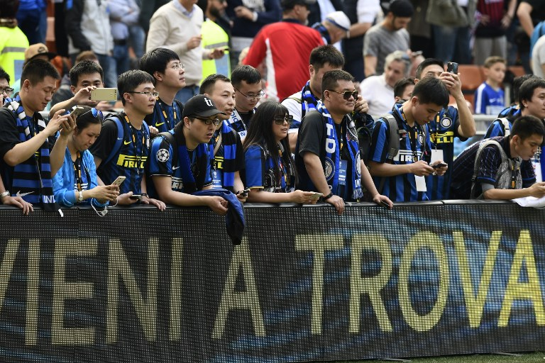 Chinese supporters of Inter Milan wait for the start of the Italian Serie A football match Inter Milan vs AC Milan at the San Siro stadium in Milan on April 15, 2017. / AFP PHOTO / MIGUEL MEDINA