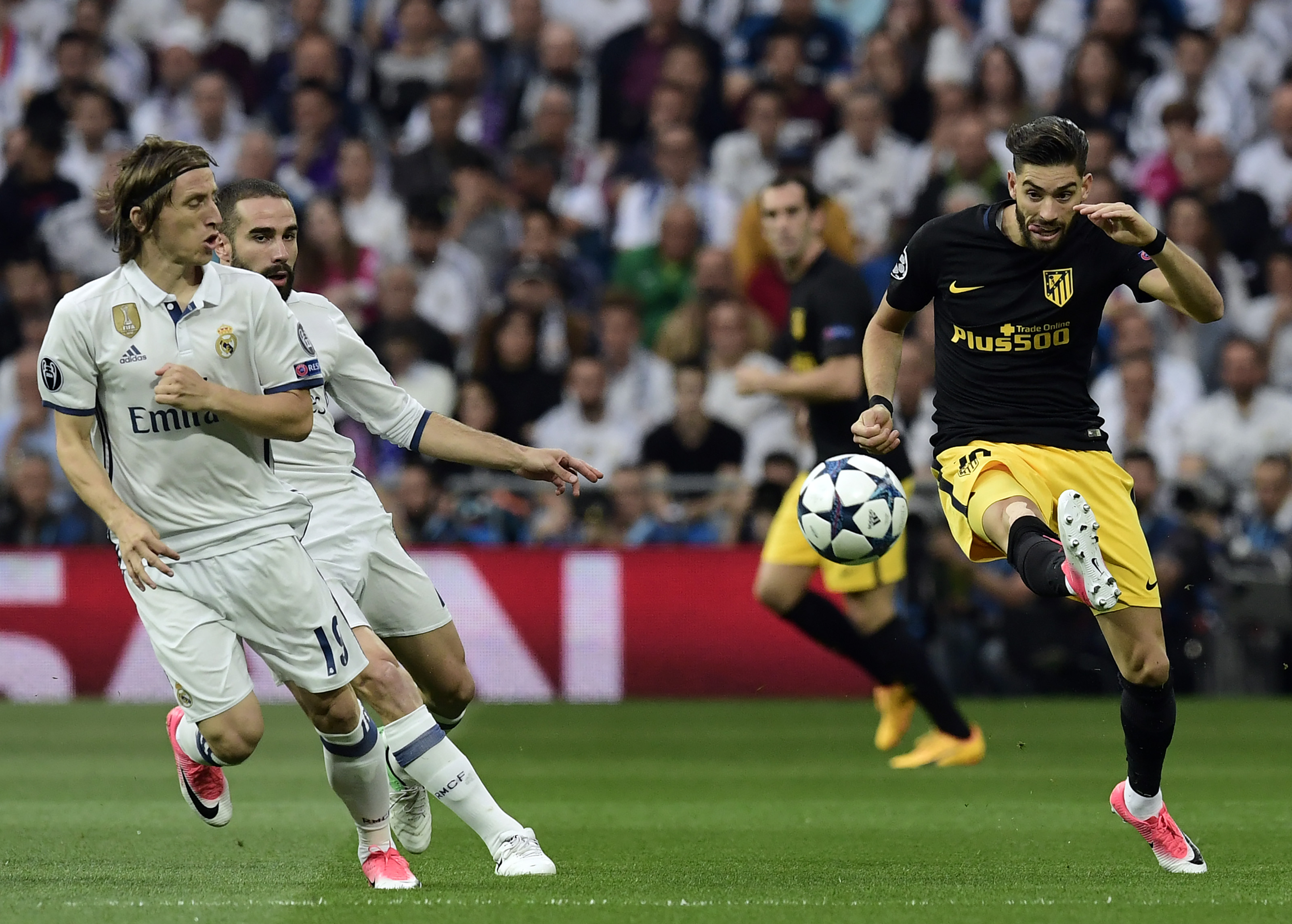 Atletico Madrid's Belgian midfielder Yannick Ferreira Carrasco (R) vies with Real Madrid's Croatian midfielder Luka Modric (L) and Real Madrid's defender Dani Carvajal during the UEFA Champions League semifinal first leg football match Real Madrid CF vs Club Atletico de Madrid at the Santiago Bernabeu stadium in Madrid, on May 2, 2017. / AFP PHOTO / JAVIER SORIANO