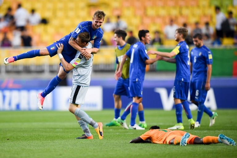 Italy's goalkeeper Andrea Zaccagno lifts up forward Luca Vido as they celebrate their victory during the U-20 World Cup quarter-final football match between Italy and Zambia in Suwon on June 5, 2017. / AFP PHOTO / JUNG Yeon-Je